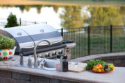 38156560 - preparing a healthy summer meal in an outdoor kitchen with gas barbecue and sink on a brick patio overlooking a tranquil lake with tree reflections